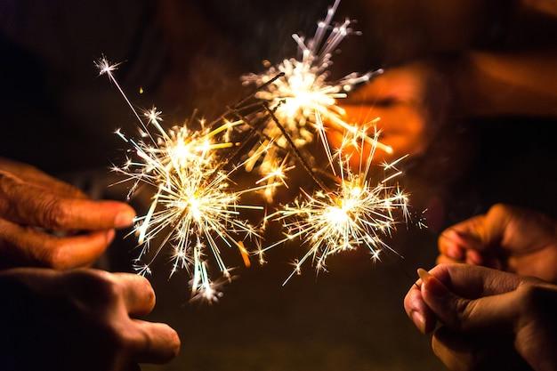 Hands of people holding sparkler, bright festive christmas sparkler.