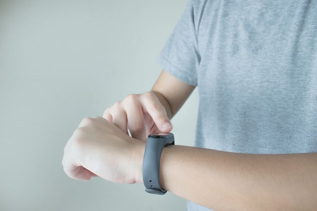 The hands of people wearing gray t-shirts are using intelligent watches to monitor heart rate.