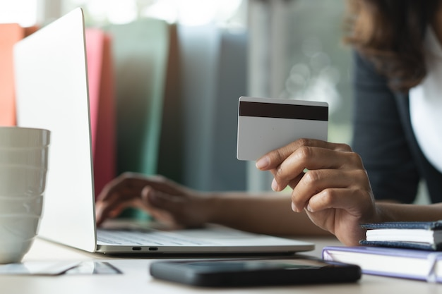 Hands of person shopping on ecommerce and using credit card.