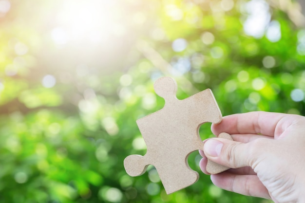 Hands person trying to connect couple jigsaw wooden puzzle piece with tree fresh background
