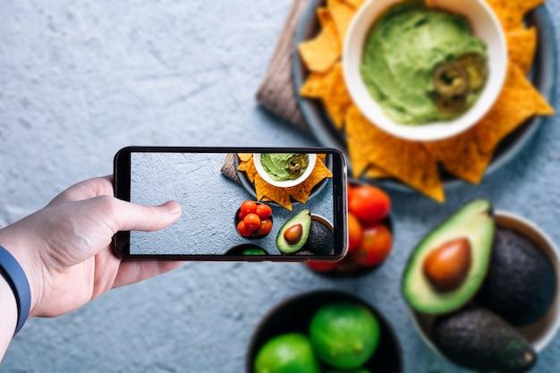 Руки, собирание смартфон, сфотографировать миску с гуакамоле. пространство для текста. выборочный фокус