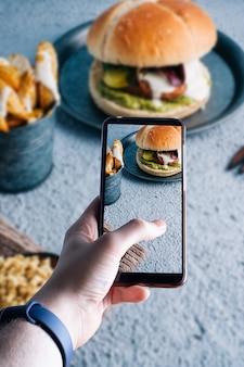 ハンバーガーの写真を撮るスマートフォンを手に取っています。テキストのためのスペース。セレクティブフォーカス