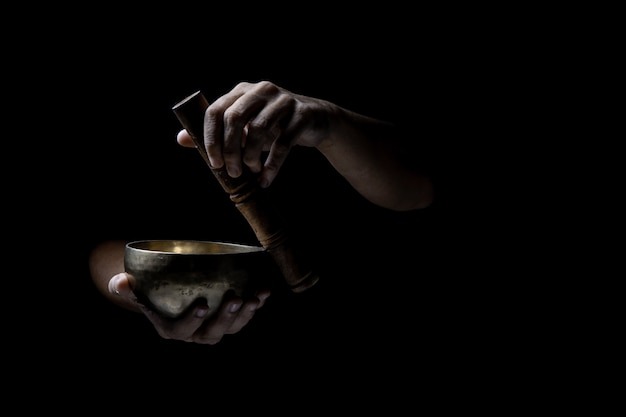 Hands  playing an old tibetan singing bowl. black background. music therapy.