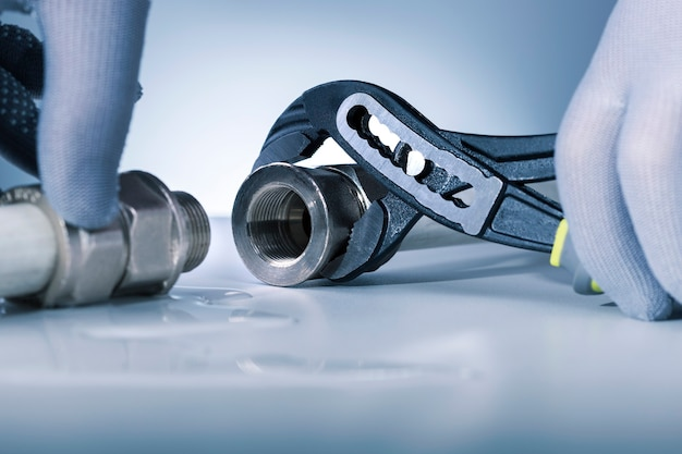 Hands of plumber with a spanner connects water pipe. plumbing repair service concept.
