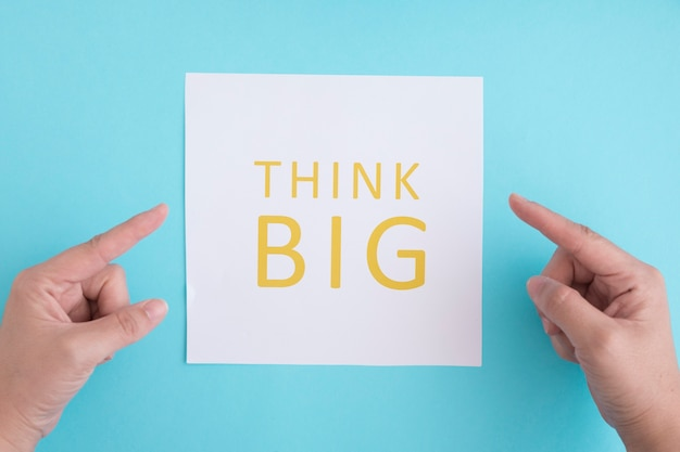Hands pointing the finger on think big text over the white paper against blue background