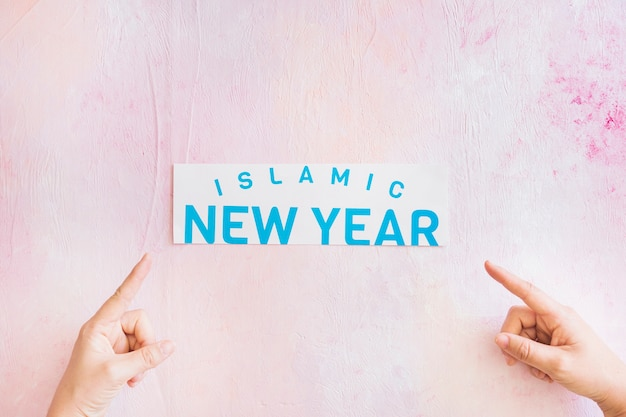 Hands pointing at islamic new year paper