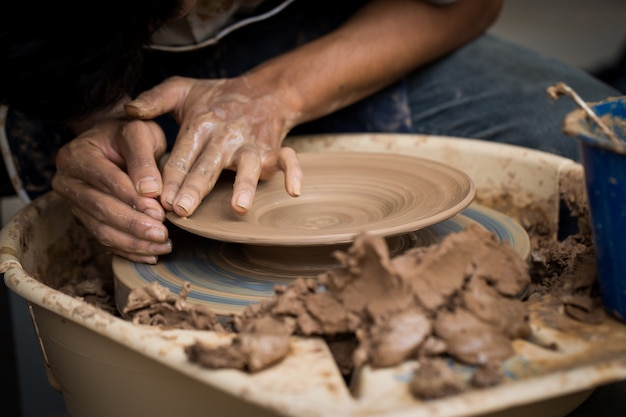 Hands of a potter, creating a dish