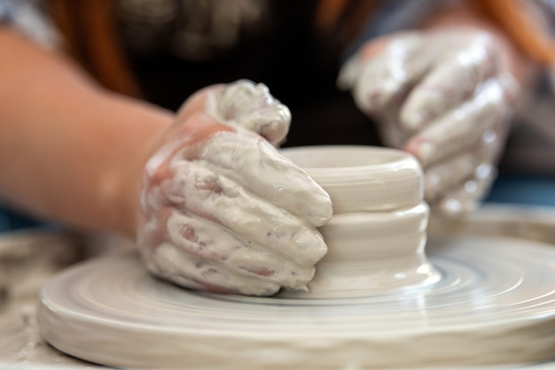 Hands of the potter. the potter makes pottery dishes on potter's wheel