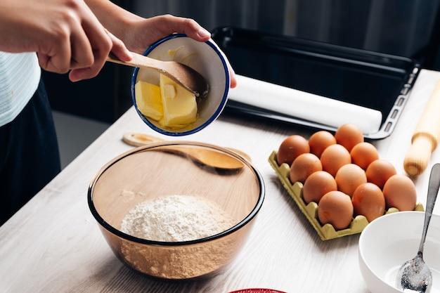 小麦粉のボウルにバターを注ぐ手