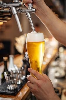 グラスに生ビールを注ぐ手