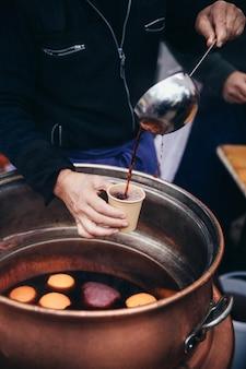 독일 gluehwein의 뜨거운 mulled 와인을 거대한 부엌 숟가락으로 종이컵에 붓는 손