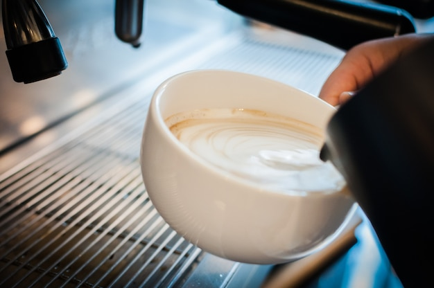ミルクを注いで新鮮なカプチーノを準備する手、コーヒーアーティストと準備の概念、新鮮な朝のコーヒー、コーヒータイム
