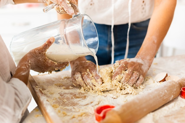Hands pouring milk to prepare dough