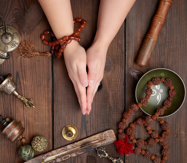 Hands in a prayer pose on a wooden brown table in the middle of vintage tibetan meditation tools