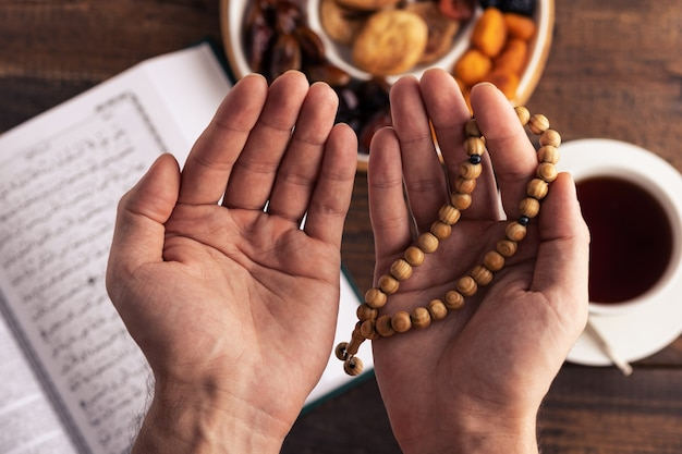 Hands of prayer with wooden rosary on background of book koran, cup tea, plate of dried fruits, iftar concept, month of ramadan, top view, closeup