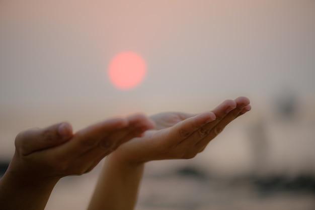日没の背景に神から祝福を祈る手。希望のコンセプト。