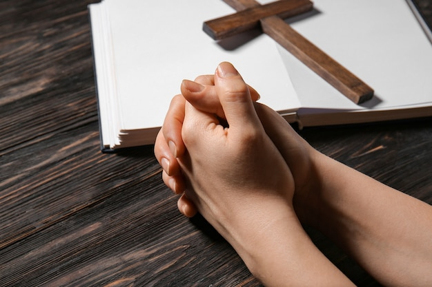 Hands of praying woman, bible and cross on wooden space