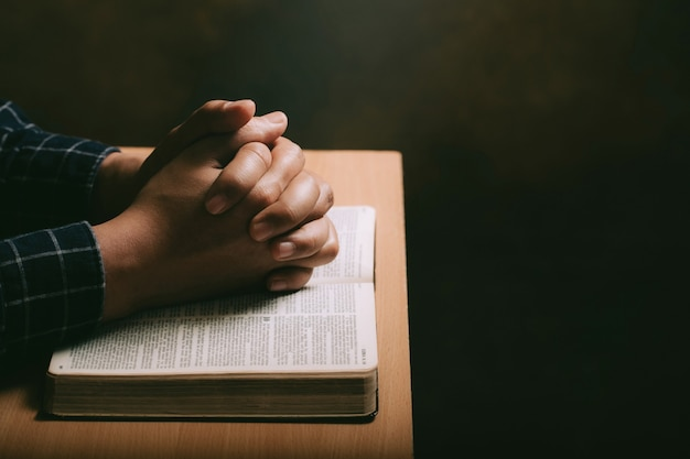 Hands of praying young man and bible on a wooden desk background. man join hands to pray and seek the blessings of god, the holy bible.