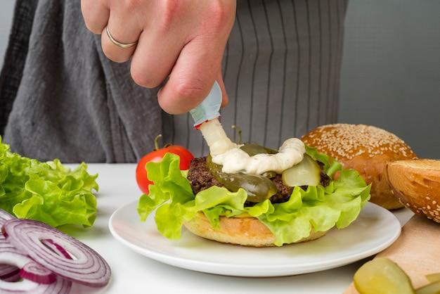 おいしいハンバーガーを準備する手