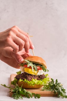 Hands preparing a big hamburger