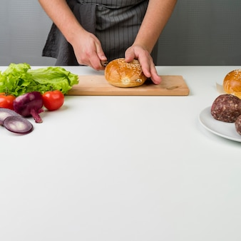 Hands preparing a delicious burger