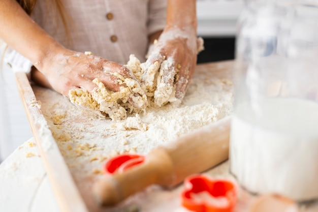 Hands preparing dough next to kitchen roller