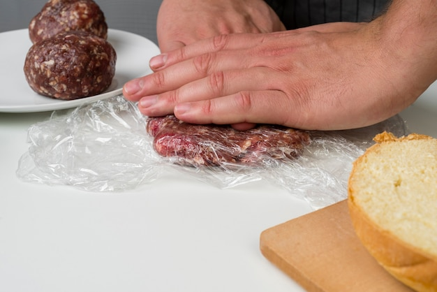 Hands preparing meat for hamburger