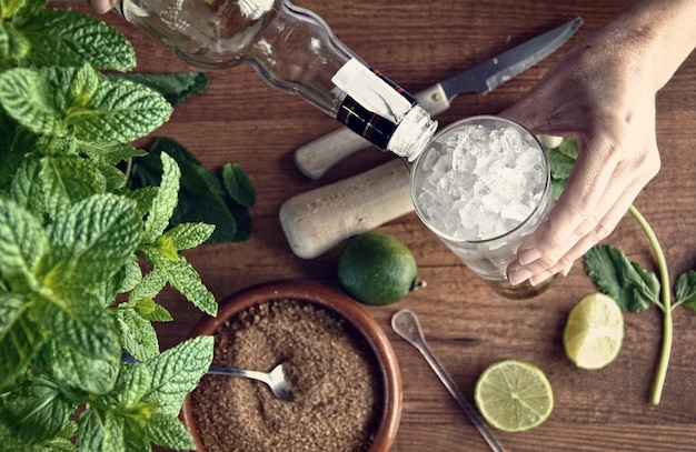 Hands preparing mojito cocktail with limes and mint