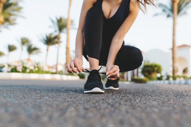 Mani di donna graziosa che allaccia i lacci delle scarpe su scarpe da ginnastica sulla strada con le palme. mattina di sole in città tropicale, allenamento, fitness, allenamento, motivazione