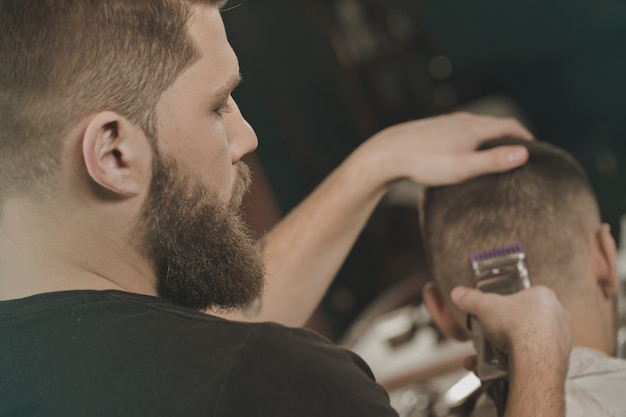 In hands of a professional.  young professional barber cutting hair