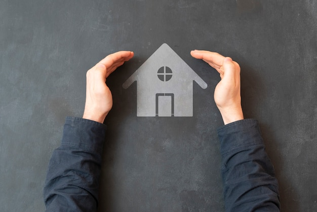 A hands protect the home icon, concept of real estate safety