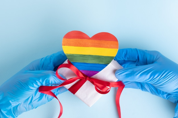Hands in protective blue gloves hold a homemade rainbow paper heart and a gift box with a red ribbon on a light blue background, copy space. safe valentine's day 2021 concept