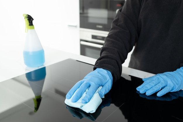 Hands in protective glove cleaning a modern electric stove with rag of a minimalist kitchen