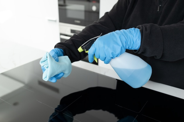 Hands in protective glove cleaning a modern electric stove with rag and spray of a kitchen