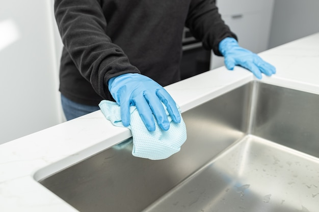 Hands in protective glove cleaning a modern sink with rag of a minimalist domestic kitchen