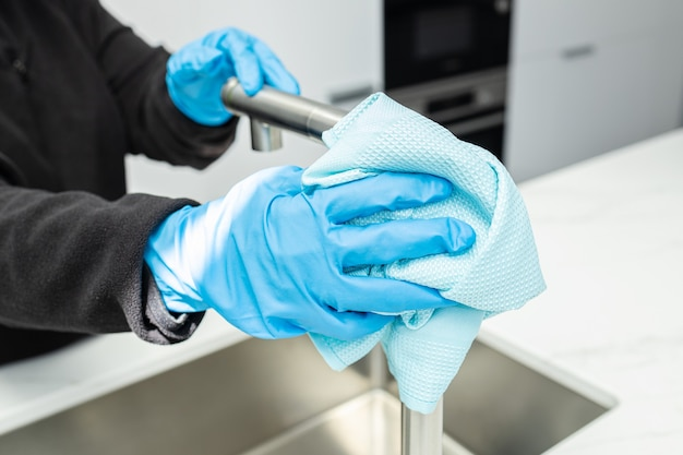 Hands in protective glove cleaning a modern tap with rag of a minimalist domestic kitchen