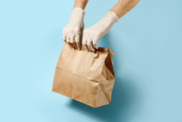Hands in protective gloves hold craft package on a blue wall with a copy space.