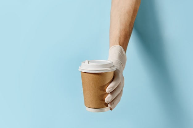 Hands in protective gloves holding a paper bag and coffee cup