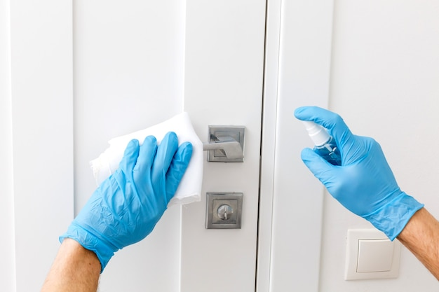 Hands in protective gloves - one holds the sprayer with an antiseptic, the other - wipes the door handle with a cloth moistened with a disinfectant solution