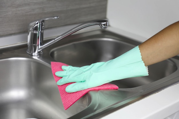 Hands in protective gloves with rag wiping sink. maid or housewife cleans house. general cleaning or regular wash up.