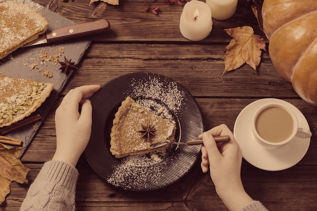 Hands and pumpkin pie on  wooden table