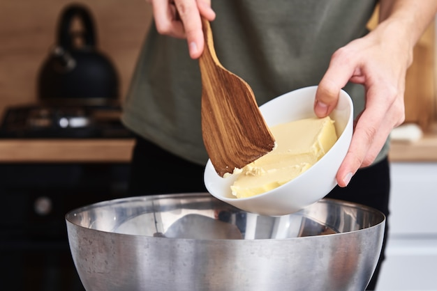 Hands put a butter in bowl.