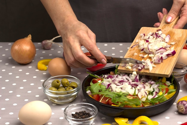 Hands put onions in  pan from  cutting board. eggs, olives, garlic, yellow pepper on the table