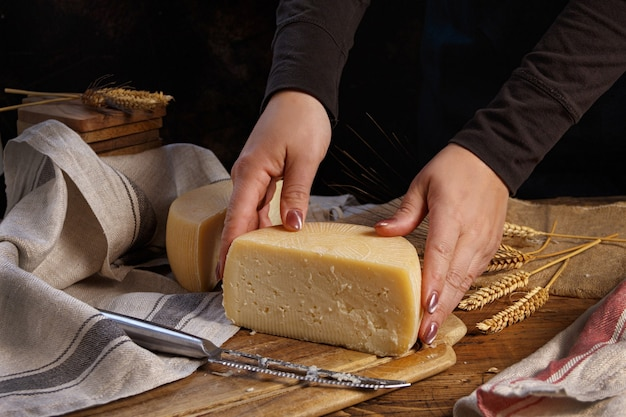 Hands put pieces of  fresh homemade cheese on a wooden board close up
