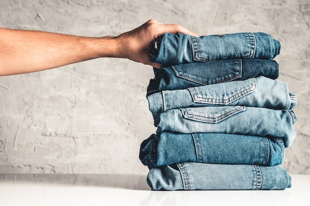 Hands, put the stack of blue jeans on gray