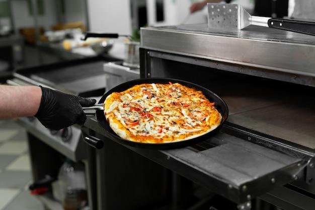 Руки кладет пиццу в духовку