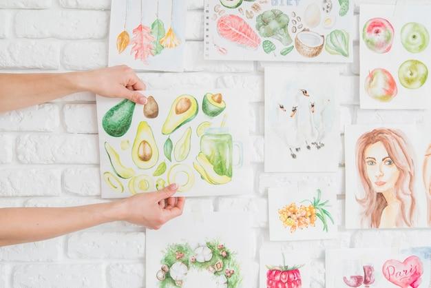 Руки кладут фруктовый рисунок на стену