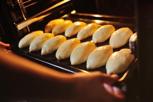 オーブンに生のイーストパイを入れた天板を入れた手