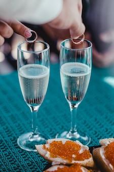 Руки кладут кольца в свадебные бокалы с игристым шампанским
