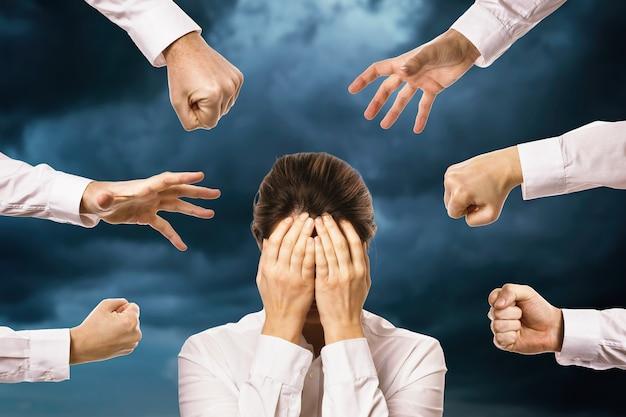 Руки тянутся к человеку, закрывающему лицо на фоне облачного неба. концепция на тему страха и кризиса в современном обществе.